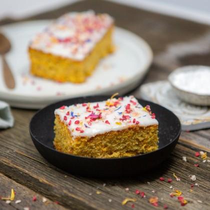 Karotten-Nuss Kuchen mit Zitronenglasur und bunten Blüten