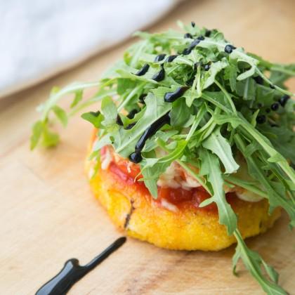Gebratene Polenta mit Tomaten und Käse überbacken, mit Rucola garniert