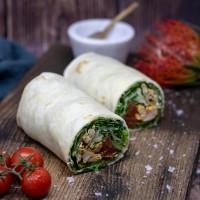 Chicken-Wrap mit Rucola, Tomatenmarmelade, Gurken und Avocados